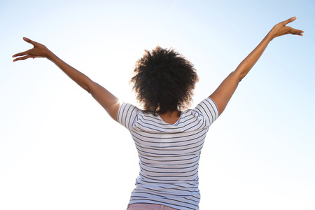 Rear view portrait of young female standing outdoors against sky with her hands raised
