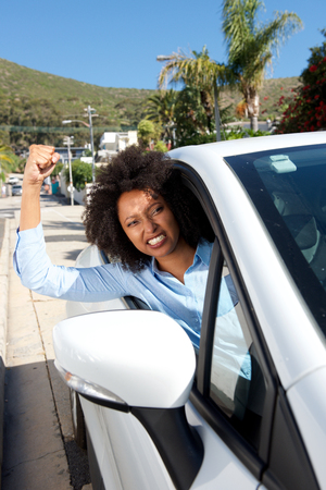Portrait of angry female car driver showing her fist while driving