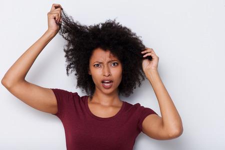 close up portrait de jeune femme africaine tirant les cheveux bouclés bouclés et en regardant inquiet