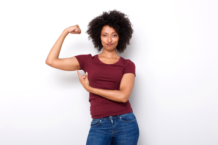 Portrait of fit young african woman pointing at arm muscles on white background
