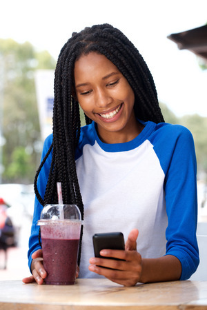 Portrait of smiling young black woman using smartphone at cafe