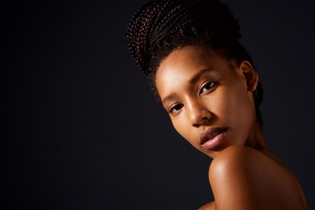 Close up portrait of pretty african woman with naked shoulders looking at camera Stock Photo