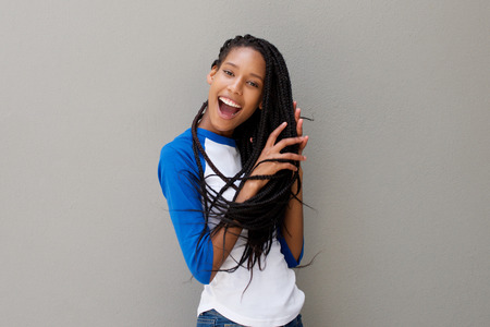 Portrait of young black woman with braided hair laughing against gray wall