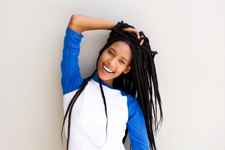 Portrait of attractive young black woman with braided hair posing against a wall Stock Photo