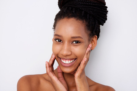 Close up portrait of african american female fashion model with hands by face against white background