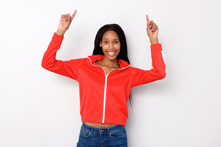 Portrait of cheerful young african woman pointing fingers up on white background