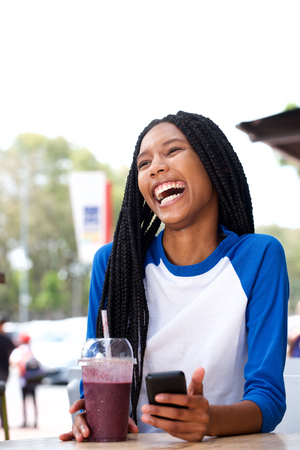 Portrait of cheerful african american girl laughing with mobile phone at cafe Stock Photo