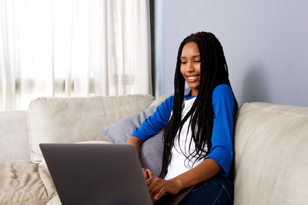 Portrait of attractive young african woman sitting at home working on laptop Stock Photo