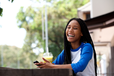 Portrait of cool young african woman with cellphone laughing at outdoor cafe