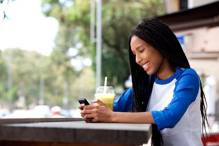 Side portrait of happy young african woman sitting at outdoor cafe using cellphone