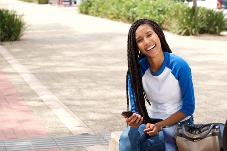 Portrait of attractive young african woman sitting outside with smart phone and smiling Stock Photo