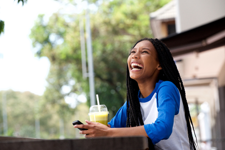 Portrait of happy young african american woman with mobile phone at cafe Stock Photo