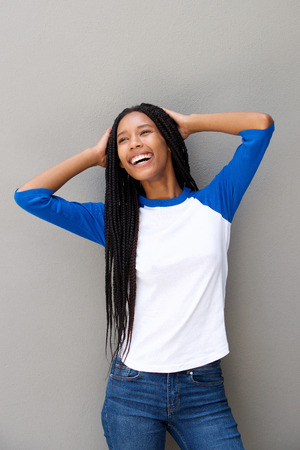 Portrait of cheerful young black woman with braided hair smiling against gray wall