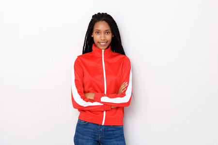 Portrait of beautiful young woman in red jacket standing with arms crossed on white background