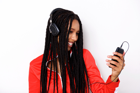 Close up portrait of cool young african woman listening music with mobile phone and headphones on white background Stock Photo