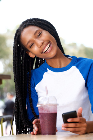 Portrait of beautiful young african woman sitting at cafe with juice and mobile phone Stock Photo