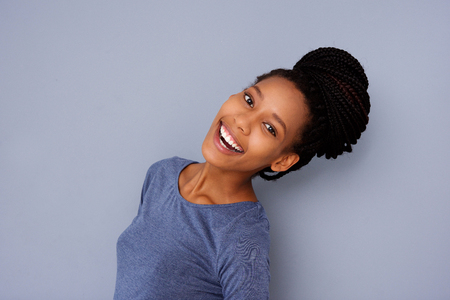 Close up side portrait of beautiful girl with braided hair bun laughing on gray background Stock Photo