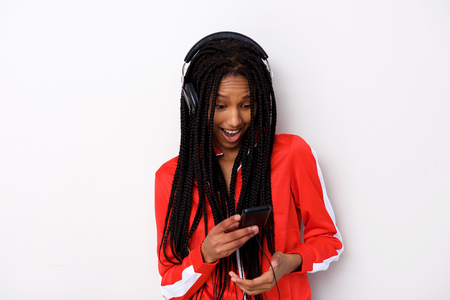 Portrait of young african woman with headphones looking at smart phone Stock Photo