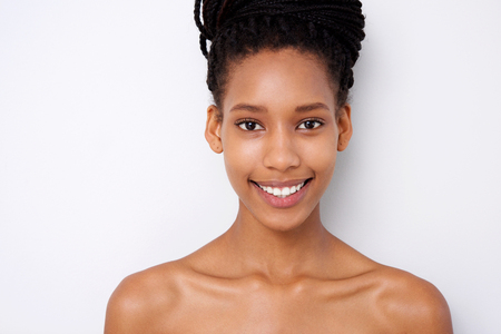 Close up portrait of beautiful young black woman against white background with naked shoulders