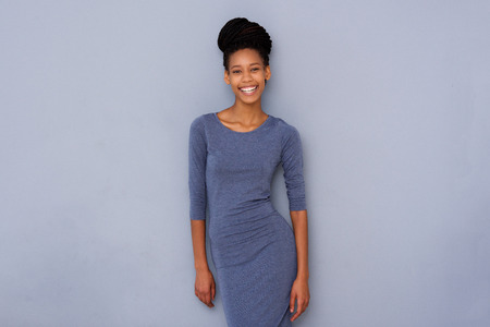 Portrait of young black woman smiling against gray wall