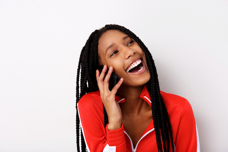 Close up portrait of cheerful young woman with braided hair talking on mobile phone and laughing