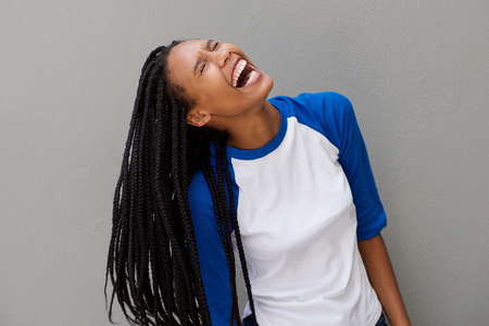 Portrait of cheerful young black woman with long braided hair laughing on gray background