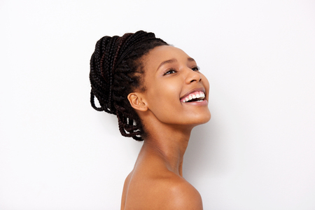 Close up portrait of pretty african woman looking away and smiling with naked shoulders Stock Photo