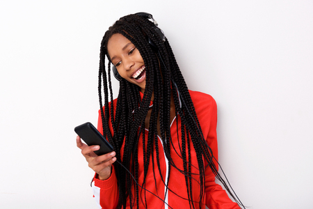 Portrait of cool young african american woman listening music with headphone and mobile phone on white background Stock Photo