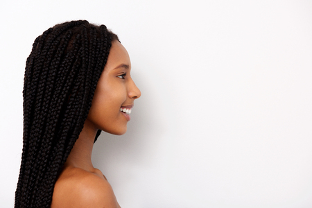 Close up side portrait of smiling african young woman with braids on white background
