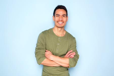 Portrait of handsome mature asian man in green full sleeves t-shirt standing with his arms crossed over blue background
