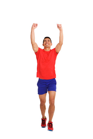 Full length portrait of happy asian man running with arms raised and clenched fist on white background