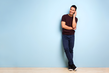 Full body portrait of stylish mature asian man standing by blue wall and making a phone call