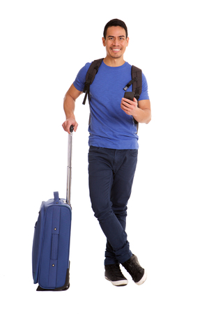 Full length portrait of handsome mid adult asian man standing with suitcase and mobile phone over white background