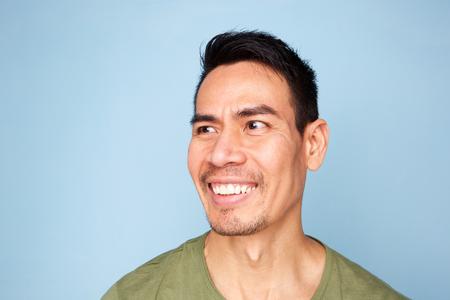 Close up portrait of smiling older asian man on blue background