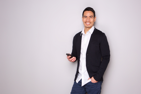 Portrait of handsome mature man with phone on gray background Stockfoto