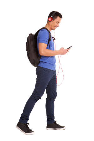 Full body side portrait of happy mature man holding cellphone with backpack and headphones on white background Imagens