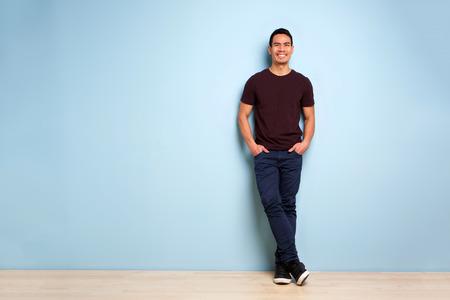 Full body portrait of fashionable asian man standing with hands in pocket by the blue wall Stock Photo