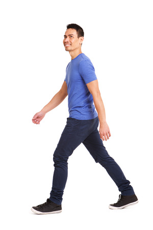 Full length side portrait of happy asian man walking over white background 版權商用圖片
