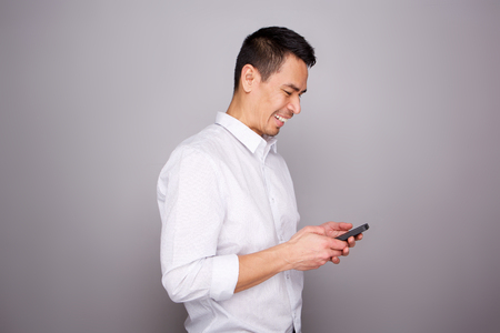 Portrait of smiling middle aged man reading text message on his mobile phone on gray background Stockfoto