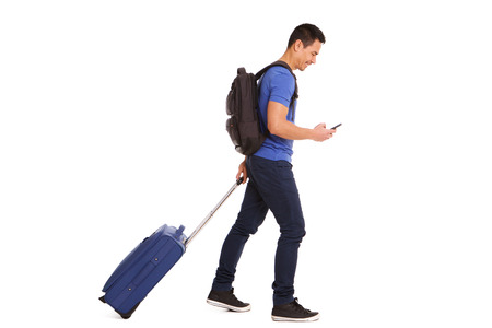 Full body side portrait of smiling mature man walking with suitcase and cellphone on white background