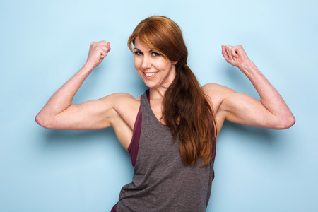 Portrait of happy mature woman flexing bicep muscles against blue wall