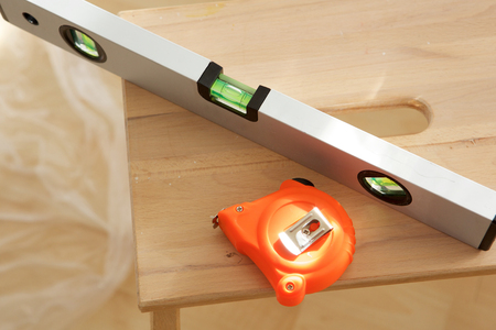 Close up portrait of measuring tape and spirit level on wooden table Stock Photo