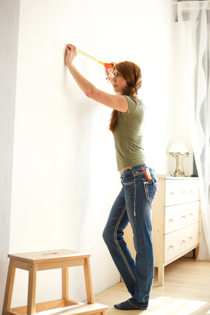 Portrait of mature attractive woman using measuring tape to mark the wall