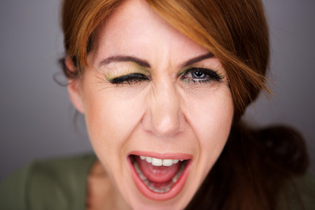 Close up portrait of cheerful middle aged woman winking eye Standard-Bild