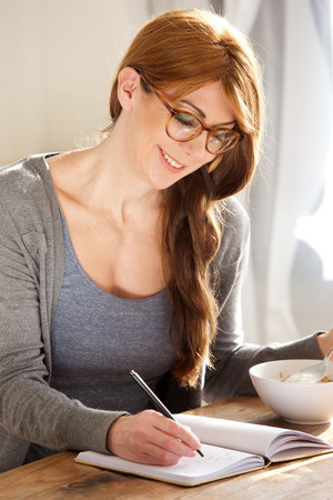 Portrait of smiling middle aged woman in glasses sitting at table and writing in a book
