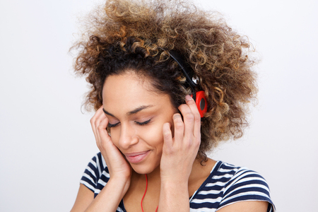 Close up portrait of happy african american girl listening to music with headphones