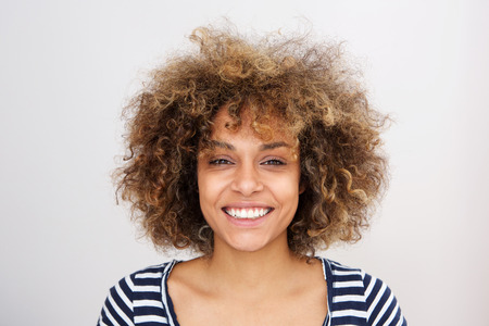 Close up front portrait of happy african american young woman smiling against white backgorund