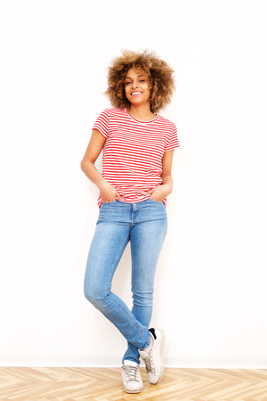 Full length portrait of smiling african american young woman against white wall
