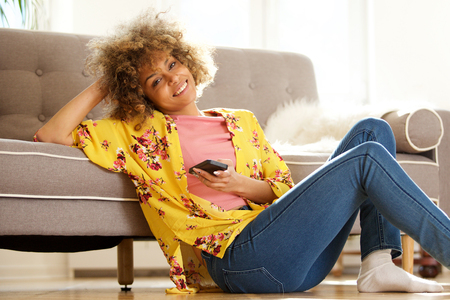 Portrait of beautiful young african american woman sitting on floor and using cellphone