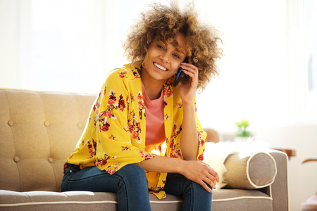 Portrait of happy young african american woman sitting on sofa talking on mobile phone Stockfoto